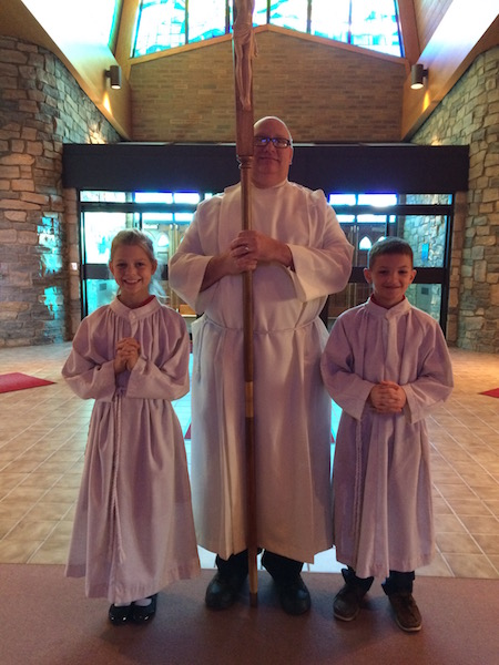 Mass is ready to begin as two student servers and priest begin to process in to church