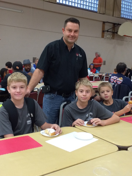 Dad and sons enjoy the Dads and Donuts event before school
