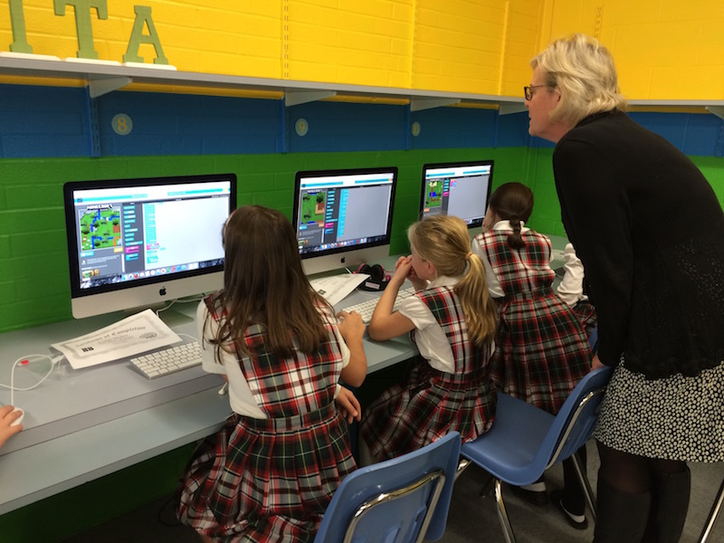 Teacher observes students progress on the iMacs