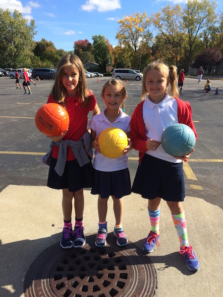 three girls hold volleyballs at recess