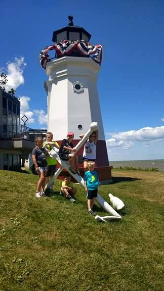 Students pose in front of a lighthouse and anchor while on summer vacation.