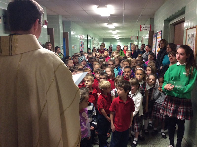 Fr. Tom blesses the school as the student body listen