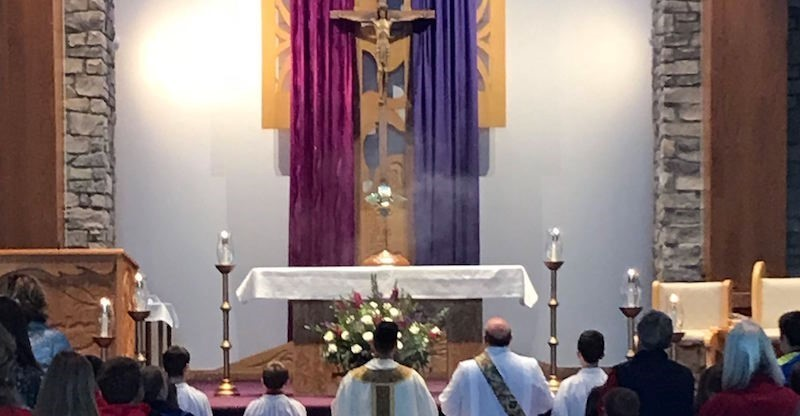 altar adorned in advent pink and purple with the priests and servers kneeling in eucharistic devotion