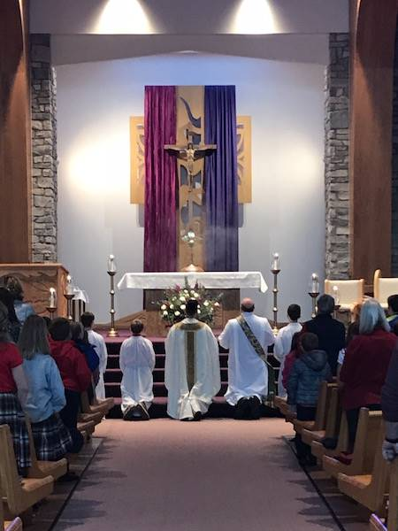 church altar with advent pink and purple with celebrants and server kneeling in eucharistic adoratio