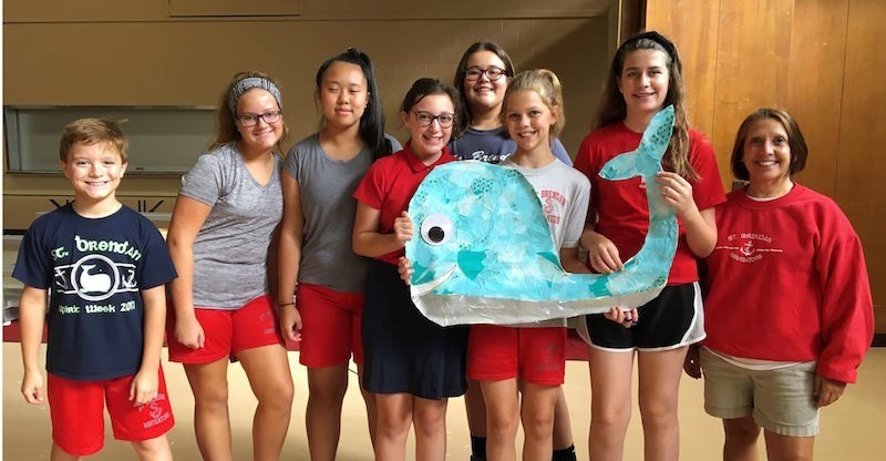 7th gade pose for a picture with the whale they made for the rally