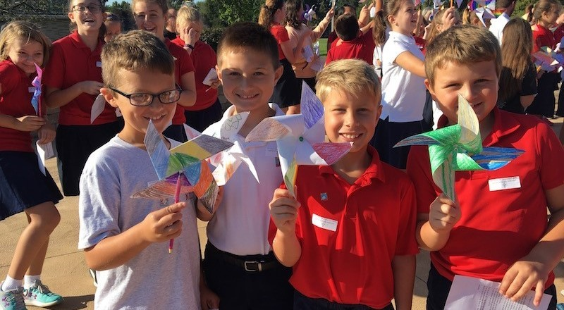Students show their pinwheels for peace