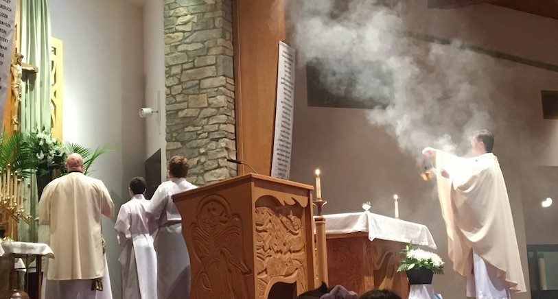 Deacon Bob and student servers look on as Fr. Tom gives blessing with incense during a recent school mass