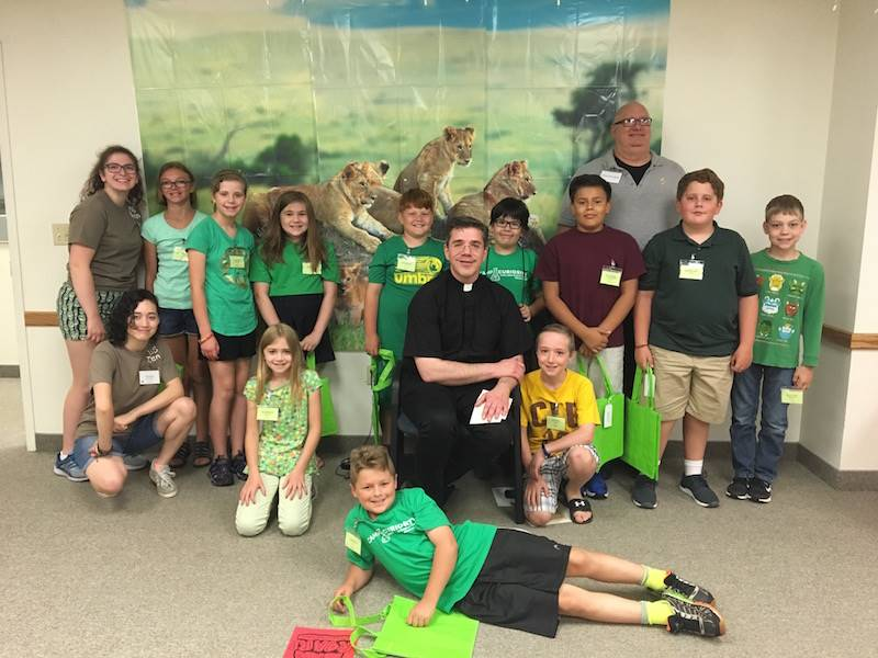 students hear about saints from Fr. Tom and Deacon Bob