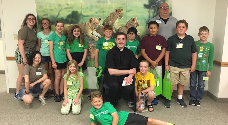 students with Fr. Tom and Deacon Bob pose for a picture during bible school
