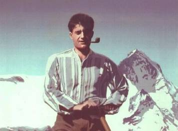 Blessed Pier Giorgio Frasatti with a pipe in front of a mountain photo taken from his website
