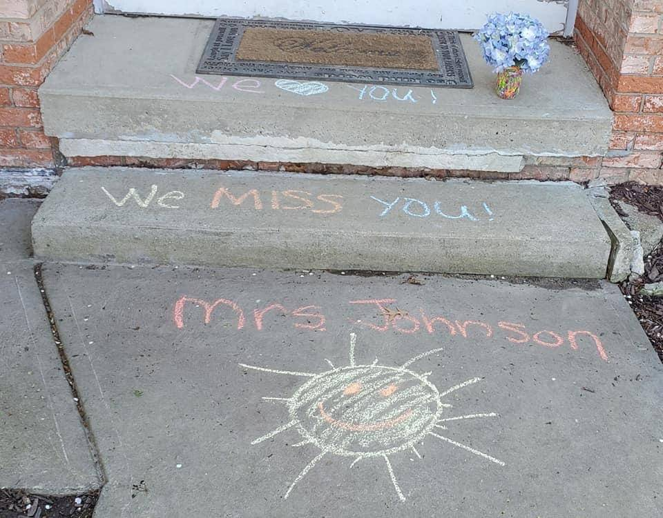 chalk drawing of a sun reading we miss you mrs johnson