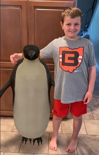 boy standing next to penguin