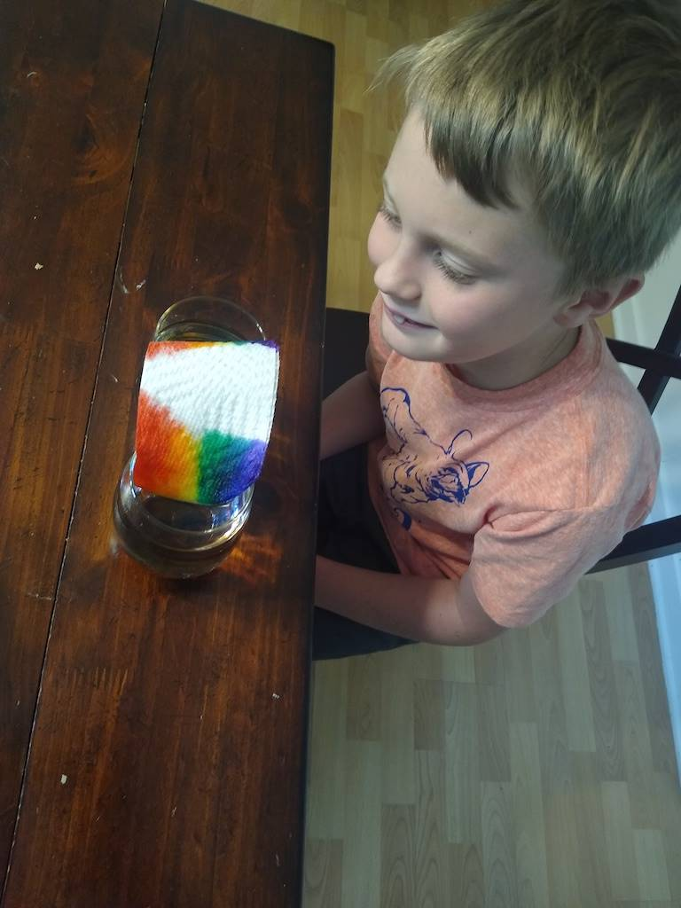 boy looks at the rainbow he made