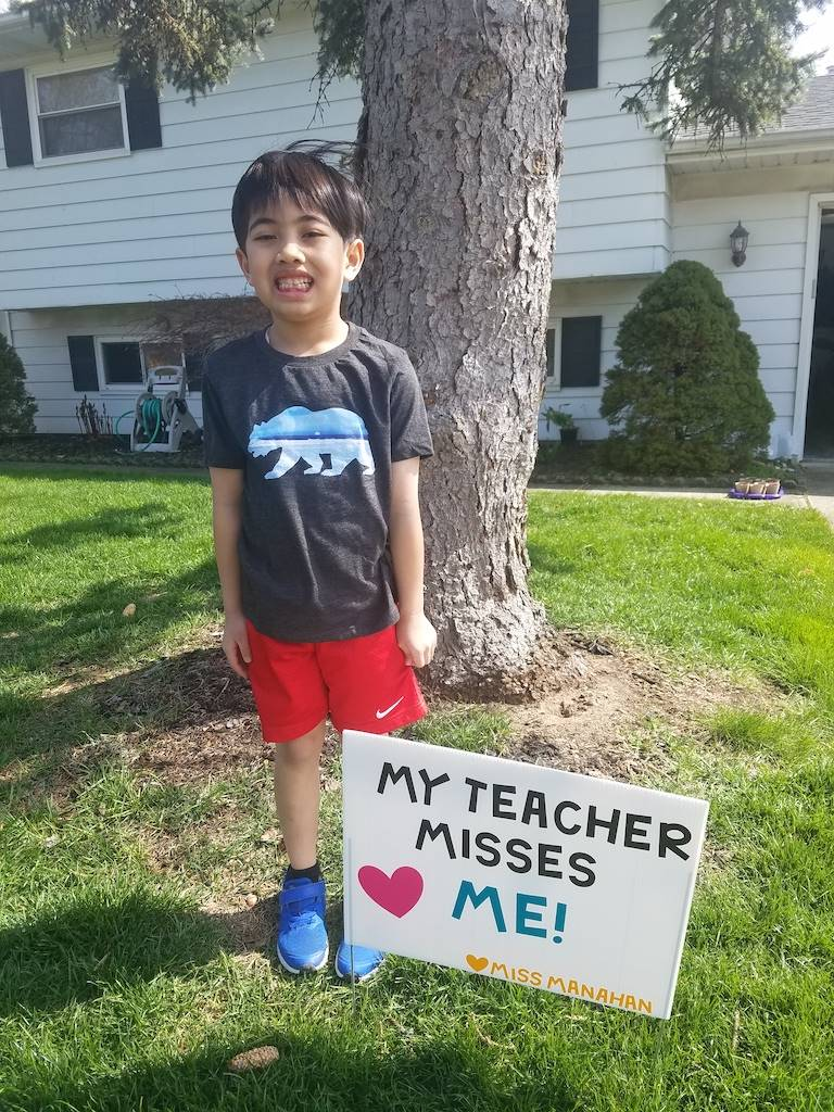 boy standing by sign reading my teacher misses me sign