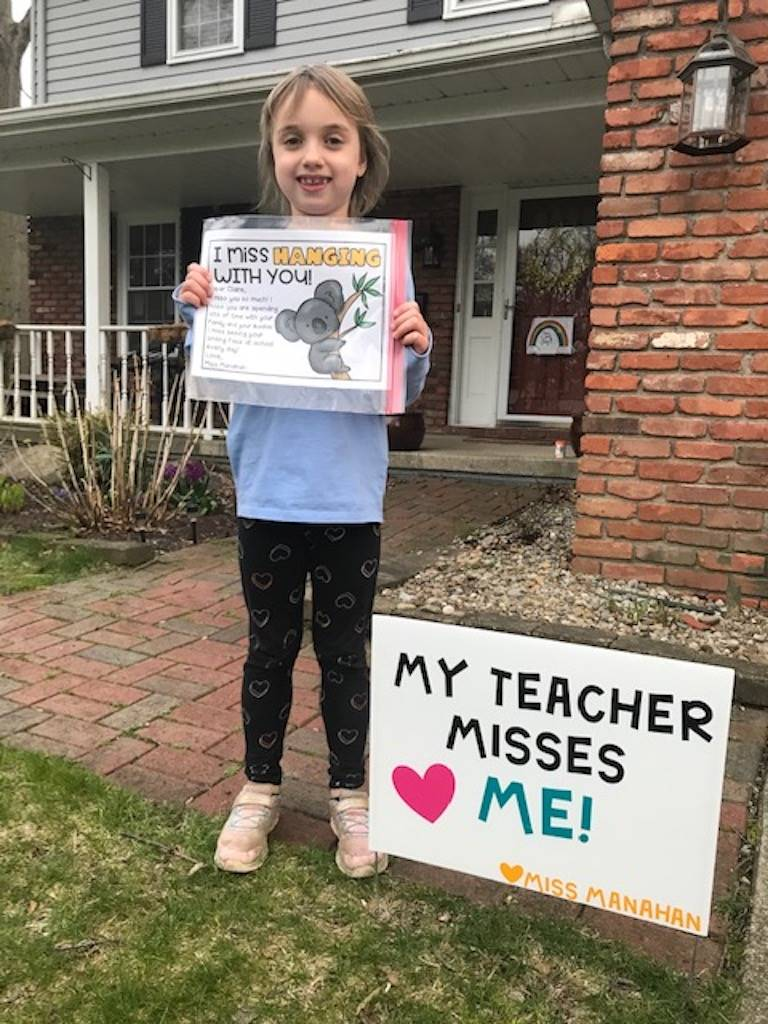 girl standing by sign reading my teacher misses me sign