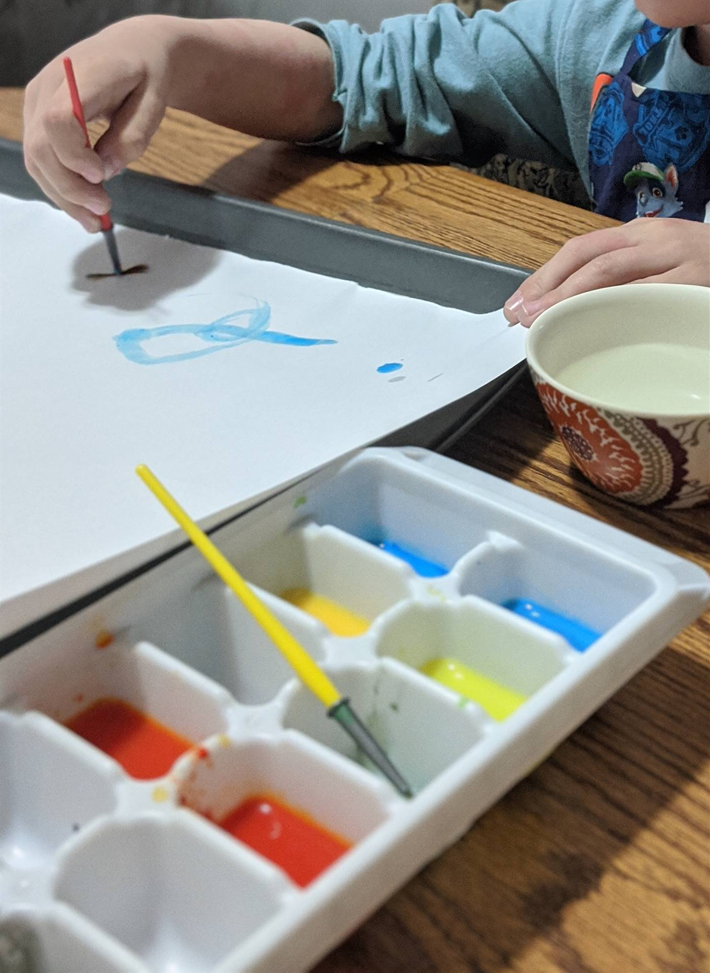 student painting using an ice cube tray as the color palette