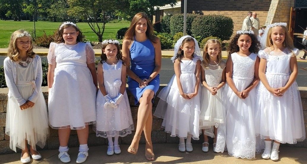 Girls pose in their first communion dresses with their teacher