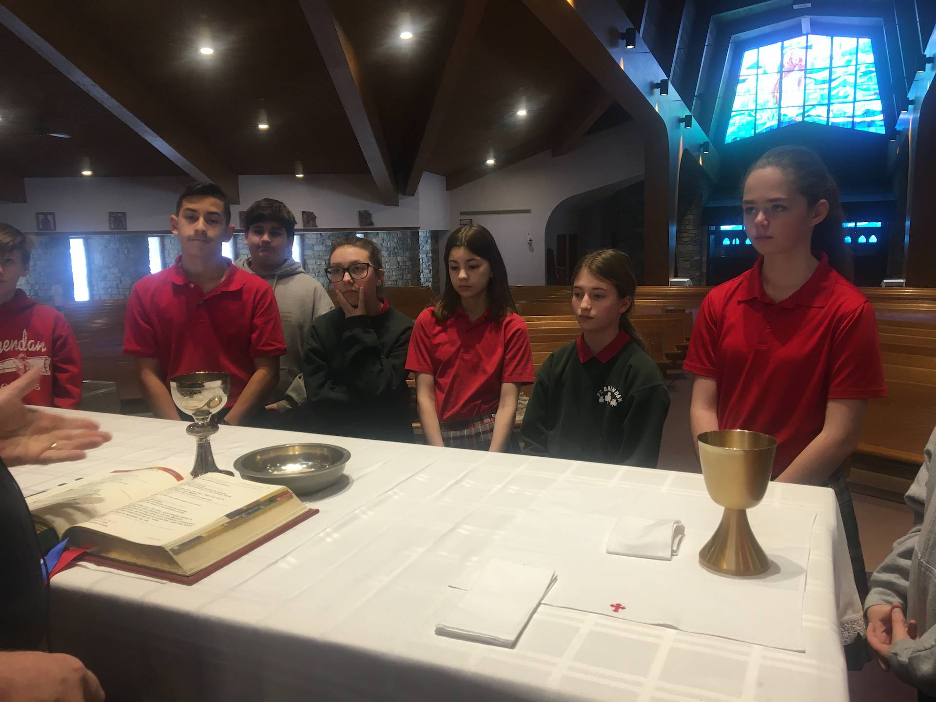 students stand around the altar learning about the Sacrament of eucharist