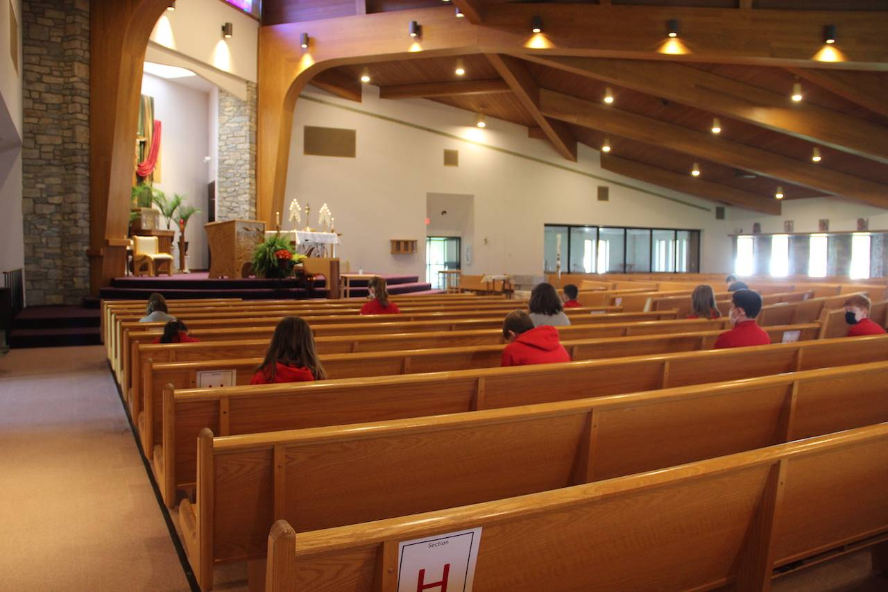 students pray in church during adoration