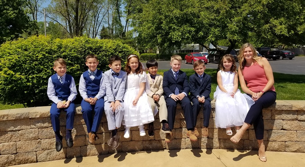 students and teacher pose for a picture in their sunday best for first communion