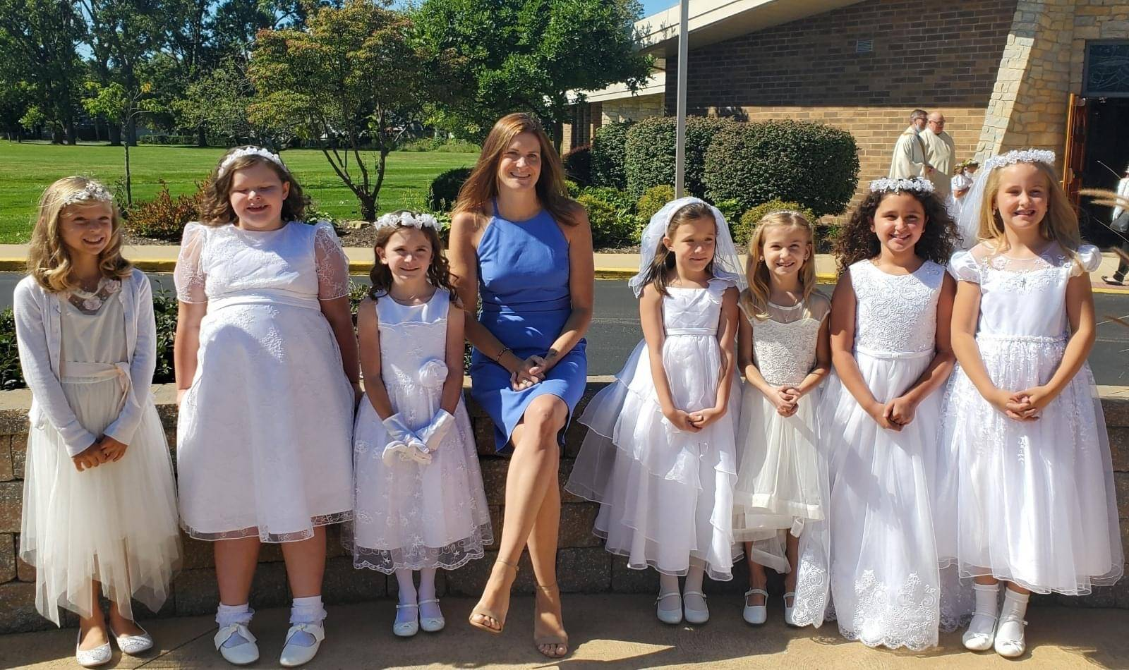 fall communion class delayed from COVID, teacher and girls in white dresses pose for a picture