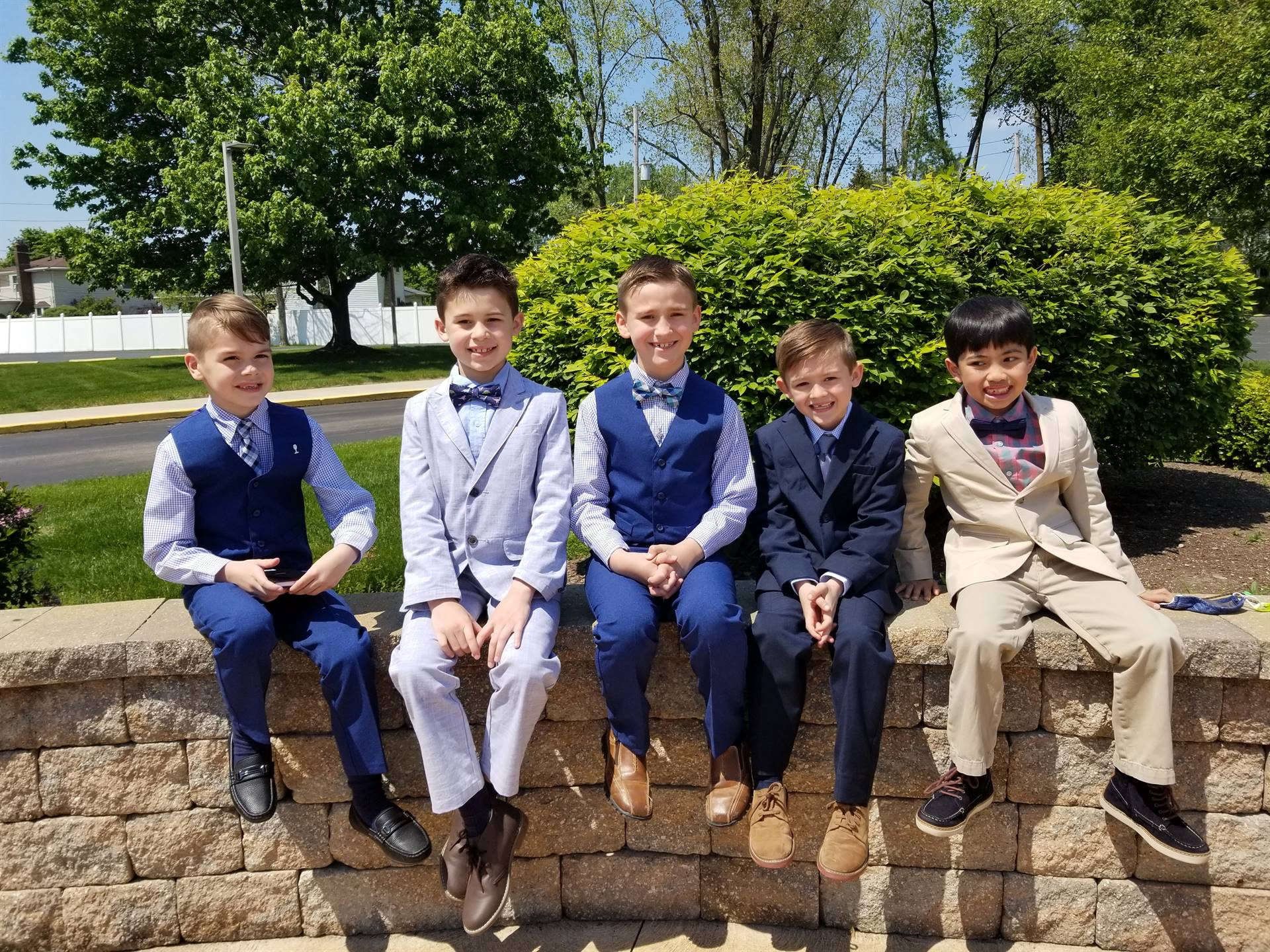 boys in suits smile after their first communion