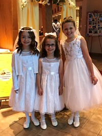 three girls smile for the camera to show off their First Communion dresses