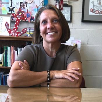 Miss Onacila, Principal of St. Brendan School, sits behind her desk
